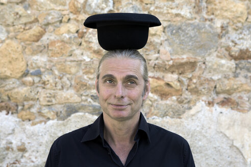 Portrait of man at stone wall balancing a bowler hat on his head - PSTF00350