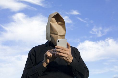 Man with paper bag above his head using cell phone - PSTF00362