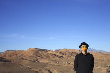 Morocco, Ounila Valley, man wearing a bowler hat with an orange in front of his face - PSTF00383