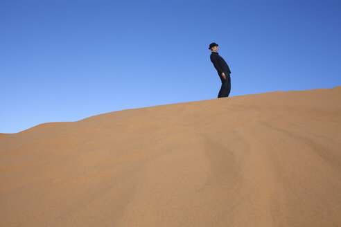 Morocco, Merzouga, Erg Chebbi, man wearing a bowler hat standing crooked on desert dune - PSTF00392