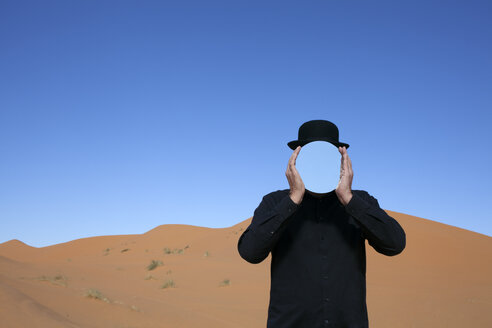 Morocco, Merzouga, Erg Chebbi, man wearing a bowler hat holding mirror in front of his face in desert dune - PSTF00395