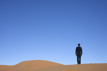 Morocco, Merzouga, Erg Chebbi, rear view of man wearing a bowler hat standing on desert dune - PSTF00398