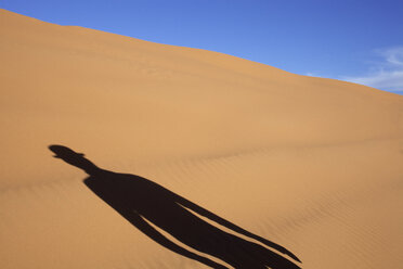 Morocco, Merzouga, Erg Chebbi, shadow of man wearing a bowler hat in desert dune - PSTF00401