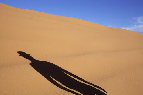 Morocco, Merzouga, Erg Chebbi, shadow of man wearing a bowler hat in desert dune - PSTF00401
