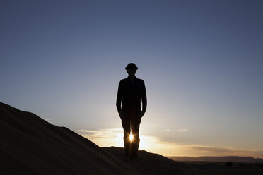Morocco, Merzouga, Erg Chebbi, silhouette of man wearing a bowler hat standing on desert dune at sunset - PSTF00404