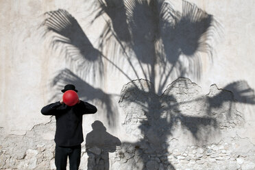 Morocco, Essaouira, man wearing a bowler hat holding red balloon in front of his face at a wall - PSTF00413