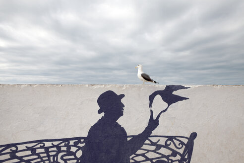 Morocco, Essaouira, wall painting of man wearing a bowler hat with seagull - PSTF00419