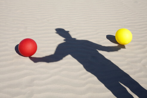 Shadow of man wearing a bowler hat and two balloons in sand - PSTF00425