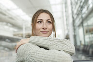 Portrait of smiling young woman at the airport sitting in waiting area - PNEF01365