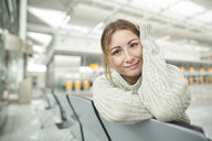 Portrait of smiling young woman at the airport sitting in waiting area - PNEF01368