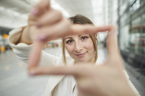 Portrait of smiling young businesswoman doing finger frame at the airport - PNEF01371