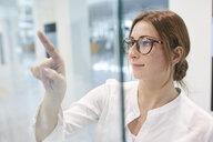 Young businesswoman touching virtual touchscreen - PNEF01374