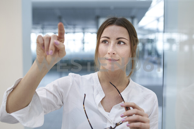 Young businesswoman touching virtual touchscreen - PNEF01377 - Philipp Nemenz/Westend61