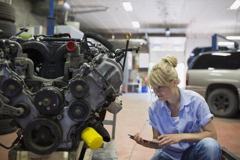 Female mechanic with digital tablet examining engine - HEROF31030