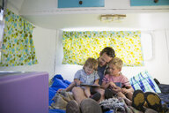 Father and sons using digital tablet inside camper - HEROF31042