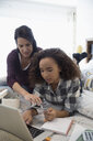 Mother teaching daughter with credit card at laptop personal finance management on bed - HEROF31100