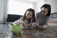 Mother and daughter counting and depositing coins into piggy bank on living room floor - HEROF31103