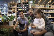 Male shop owner helping father and daughter shopping browsing terrariums in plant shop - HEROF31166