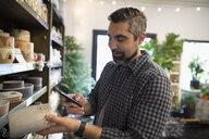 Man shopping using camera phone photographing vase in shop - HEROF31169