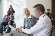 Male doctor discussing medical chart with bald female cancer patient in waiting room - HEROF31226
