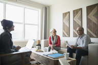 Financial advisor with laptop meeting with senior couple in living room - HEROF31286