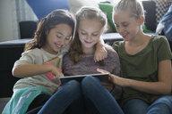 Girls enjoying play date using digital tablet in living room - HEROF31301