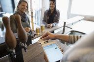 Male brewer using digital tablet credit card swiper in brewery tasting room - HEROF31316