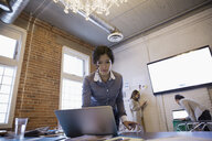 Focused businesswoman using laptop in conference room - HEROF31382