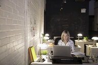 Focused businesswoman working late at laptop in open plan office - HEROF31385