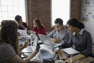 Hispanic designers meeting using laptops in conference room - HEROF31397