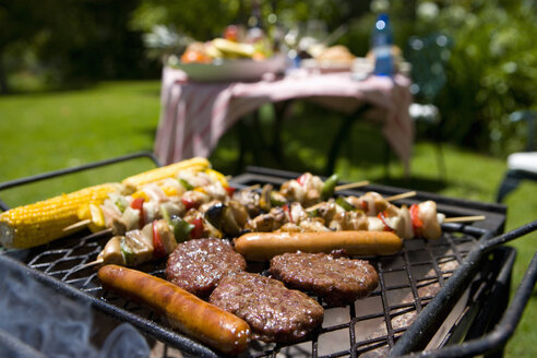 Food on barbecue by table in garden - JUIF00296