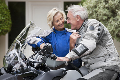 Portrait of happy senior couple on motorcycle in driveway - JUIF00308
