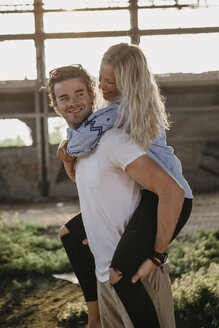 Happy young man giving girlfriend a piggyback ride in an old hall - LHPF00492