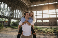 Happy young man giving girlfriend a piggyback ride in an old hall - LHPF00495