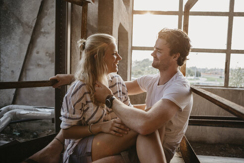 Happy young couple cuddling in an old building - LHPF00498