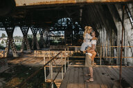 Happy young man carrying girlfriend in an old train station - LHPF00516