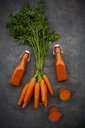 Carrot juice in bottles and glasses, bunch of carrots, from above - LVF07909