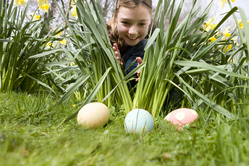Young girl finding decorated Easter eggs - JUIF00403