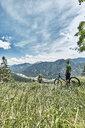 Germany, Bavaria, Isar Valley, Karwendel Mountains, mountainbiker on a trip having a break on alpine meadow - WFF00072
