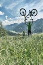 Germany, Bavaria, Isar Valley, Karwendel Mountains, mountainbiker on a trip lifting up his bike on alpine meadow - WFF00075
