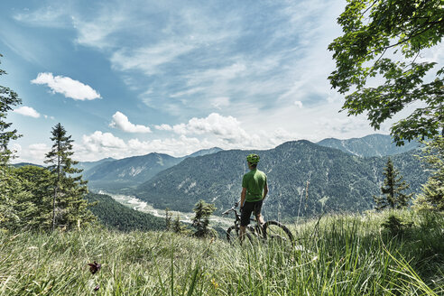Germany, Bavaria, Isar Valley, Karwendel Mountains, mountainbiker on a trip having a break on alpine meadow - WFF00078
