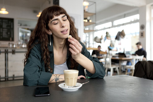 Young woman with milky coffee sitting at table in a cafe - FLLF00073