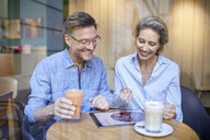 Happy woman and man using tablet in a cafe - PNEF01385