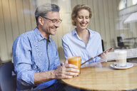Happy woman and man using tablet in a cafe - PNEF01388