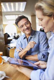 Smiling man and woman with tablet in a cafe - PNEF01391