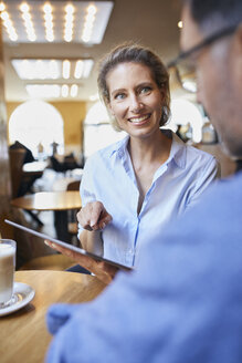 Smiling woman and man with tablet in a cafe - PNEF01394
