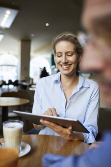 Smiling woman and man with tablet in a cafe - PNEF01397