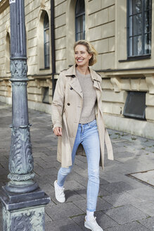 Happy woman walking on pavement in the city - PNEF01418
