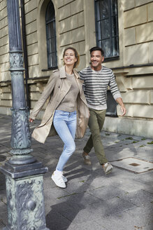 Happy couple walking on pavement in the city - PNEF01421