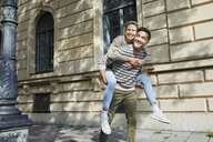 Happy man giving woman piggyback ride on pavement in the city - PNEF01424